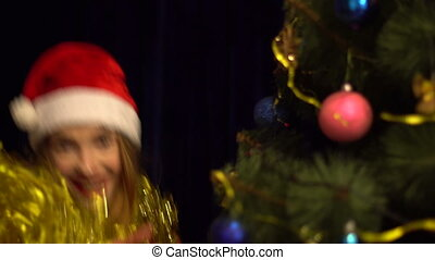 happy young girl in santa hat dancing with christmas tree and smiling