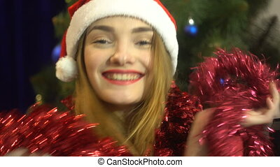 happy young girl in santa hat with tinsel on her nack smiling and looking at the camera