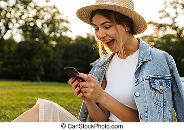 Happy young girl in summer hat sitting outdoors