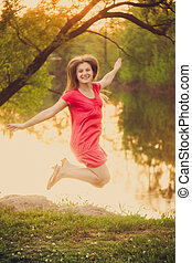 Happy Young Girl Jumping On The Park