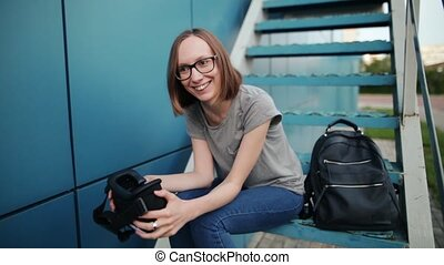 Happy young girl laughing while sitting on the stairs having experienced the technology of virtual reality. The woman is smiling with a pair of futuristic VR glasses in her hands on a blue background.