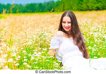 happy young girl lying in a field with daisies