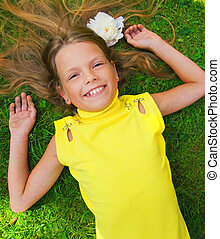Happy young girl lying on a green grass
