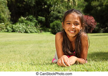 Happy young girl lying on grass
