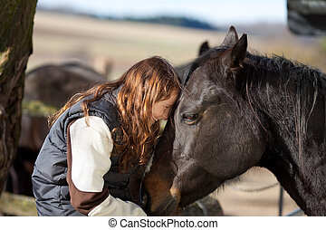 Happy young girl petting her dark bay horse