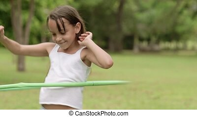 Happy young girl playing hula-hoop