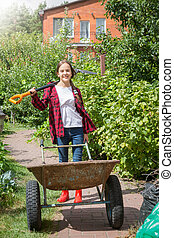 Happy young girl posing with wheelbarrow and shovel in garden at sunny day