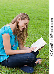 Happy young girl reading a book while sitting down in a park