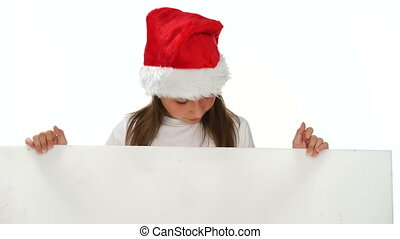 Happy young girl in a colorful red Santa hat singing Christmas carols as she holds a blank white banner for your seasonal message or greeting