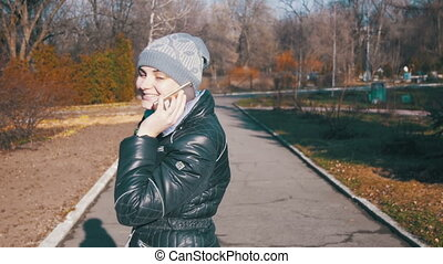 Happy Young Girl Smiling and Talking on a Smartphone in the City Park in Slow Motion
