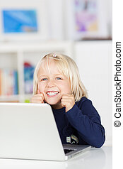 Happy young girl smiling while using a laptop