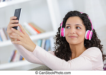 happy young girl taking pictures of herself through cell phone