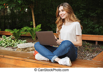 Happy young girl using laptop computer