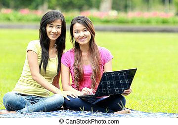 happy young girl using laptop outdoor