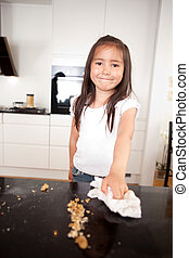 Happy Young Girl Wiping Counter - Young smiling cute girl...
