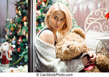 Happy young girl with a teddy bear near a decorated Christmas tree. New Year