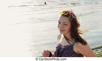 Happy young girl with flower in hair run on beach smile in camera. Sunny day.