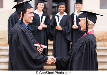 young graduate shaking hand with professor
