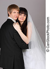 Happy young groom and bride embrace in studio on gray background; man turned his back to camera