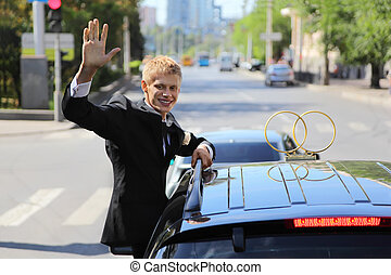 happy young groom wearing black suit waving from wedding car