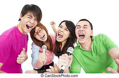 happy young group having fun singing with karaoke