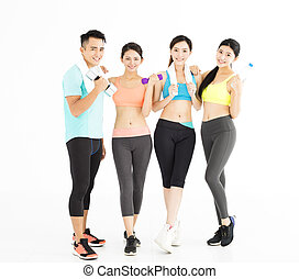 Happy young group of fit people standing in gym