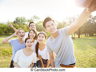 happy young group taking selfie in the park