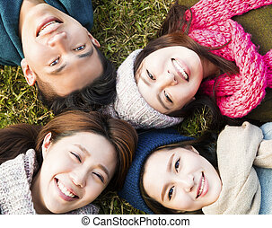 happy young group with winter wear on the grass