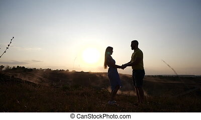Happy young guy and girl kiss and hug on the field against the backdrop of the sunset in slow motion. A loving couple kisses and enjoys a romantic setting amid the dawn of the sun. Long relationship.