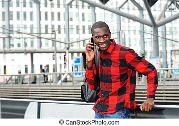 Happy young guy at railway station using cell phone
