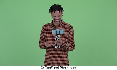 Happy young handsome African man vlogging and showing phone...
