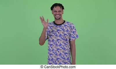 Happy young handsome African man waving hand