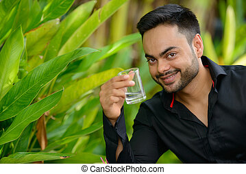 Happy young handsome bearded Indian businessman at the park