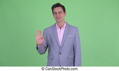 Happy young handsome businessman waving hand
