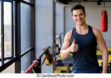 Happy young handsome man giving thumbs up at the gym