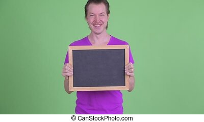 Happy young handsome man holding blackboard
