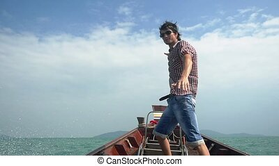 Happy young handsome man in sunglasses enjoying sailing boat...
