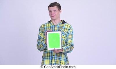 Happy young handsome man showing digital tablet and looking surprised