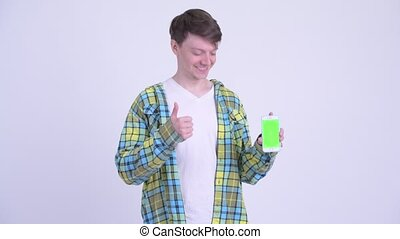 Happy young handsome man showing phone and giving thumbs up