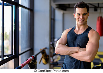Happy young handsome man thinking with arms crossed at the gym