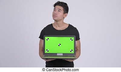 Happy young handsome multi-ethnic man showing laptop -...