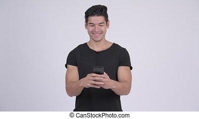 Happy young handsome multi-ethnic man using phone - Studio...