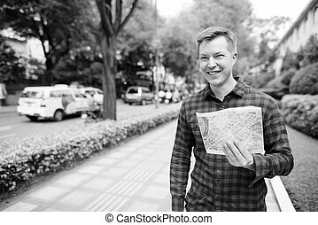 Happy young handsome tourist man looking at the map in the city streets