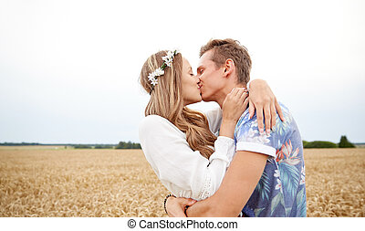 happy young hippie couple kissing in field - summer...