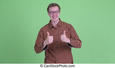 Happy young hipster man giving thumbs up and looking excited