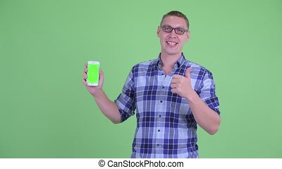 Happy young hipster man showing phone and giving thumbs up