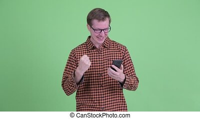 Happy young hipster man using phone and giving thumbs up