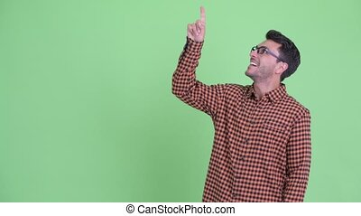 Happy young Hispanic hipster man pointing up and looking surprised