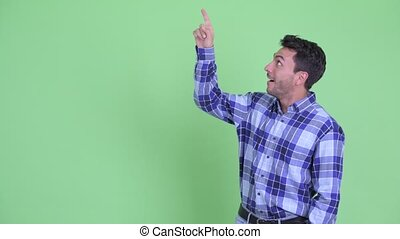 Happy young Hispanic man pointing up and looking excited