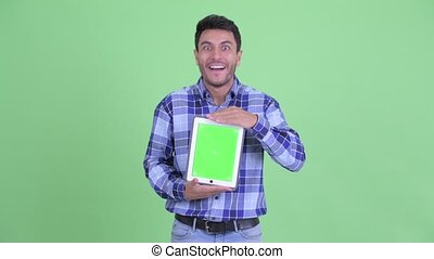 Happy young Hispanic man showing digital tablet and looking surprised